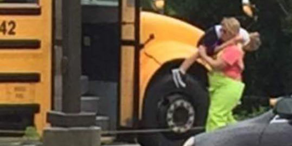 Coach carries student with new shoes to bus in the rain